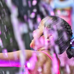 little-girl-playing-in-the-water-fountain-with-neon-lights-dancing-around-happy-playful-in-the-summer_t20_jR48Ra