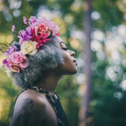 young-woman-wearing-a-flower-crown-with-a-forest-bokeh-background_t20_3JgodR
